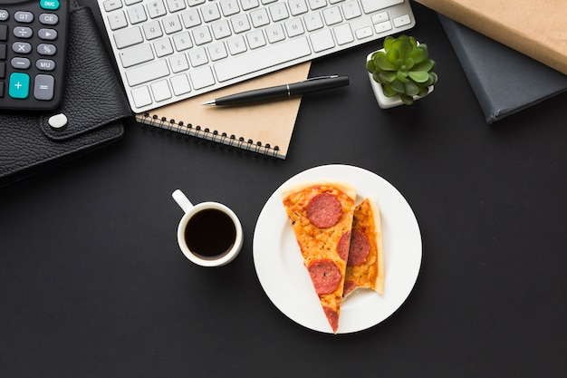 Flat lay of desktop with keyboard and pizza Free Photo
