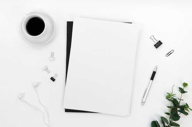 Flat lay of desktop with notebooks and paper clips Free Photo