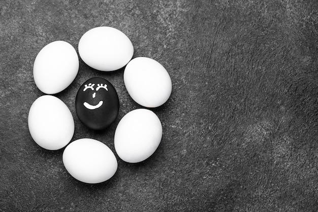 Lay piatto di uova di colore diverso con facce per vite nere importa movimento e spazio di copia Foto Gratuite