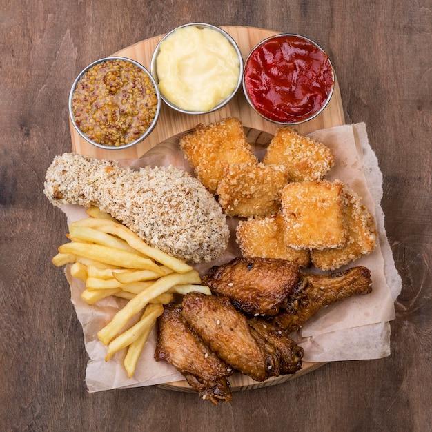 Lay piatto di diversi tipi di salsa e pollo fritto Foto Gratuite