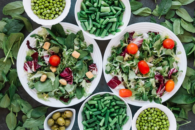 Flat lay of dishes with salads and green beans Free Photo