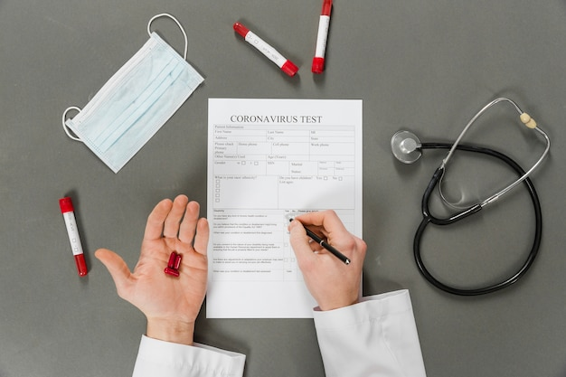 Flat lay of doctor hands filling out a coronavirus test Free Photo