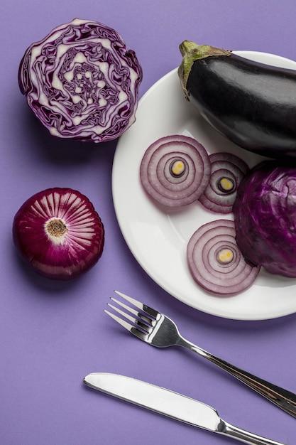 Lay piatto di melanzane e cipolla sulla piastra con posate Foto Gratuite