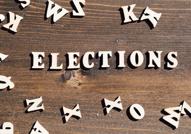 Flat lay elections lettering on wooden background Free Photo