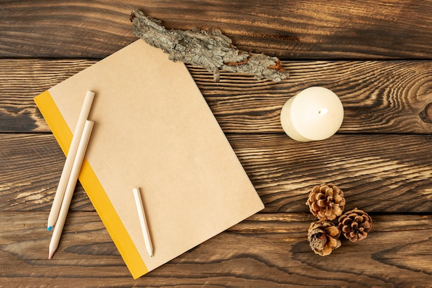 Flat lay empty notebook next to pine cones Free Photo