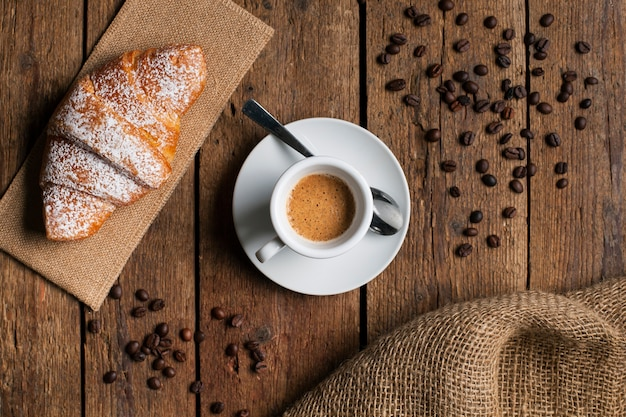 Flat lay espresso with croissant and coffee seeds Free Photo