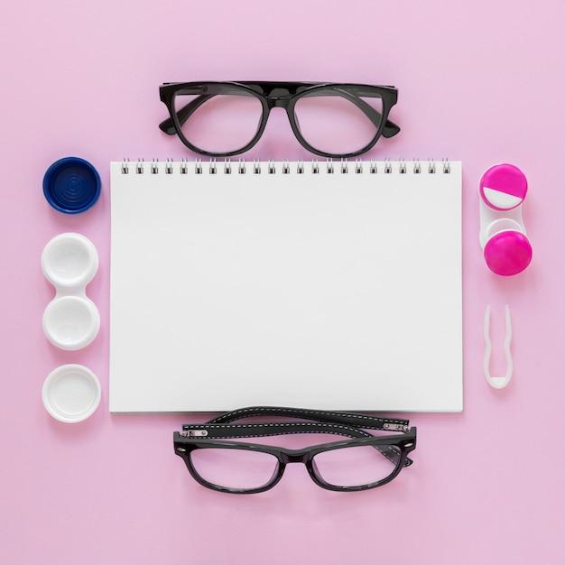 Плоские лежал аксессуары для ухода за глазами на розовом фоне с макетом ноутбука Бесплатные Фотографии