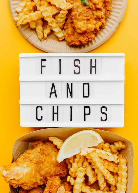 Piatto di pesce e patatine fritte con scatola leggera e salsa Foto Gratuite