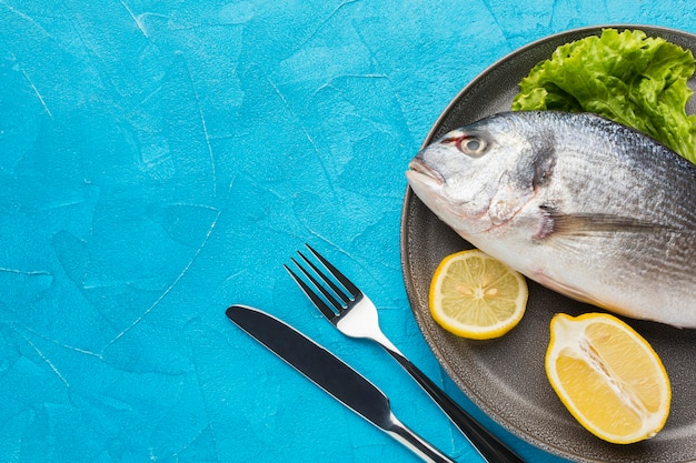 Flat lay fish with lemon on plate Free Photo