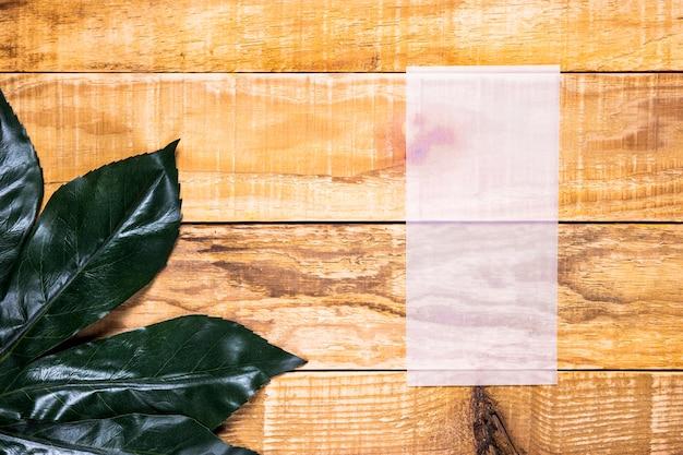 木製の背景を持つフラットレイアウト薄っぺらな紙 無料写真