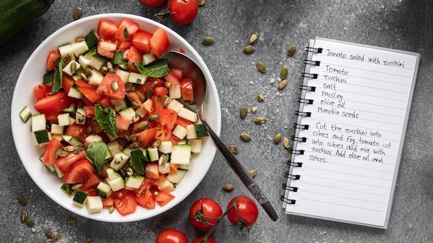 Lay piatto di ingredienti alimentari con insalata e notebook Foto Gratuite