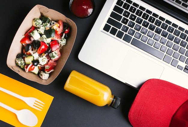 Flat lay food and laptop on black background Free Photo