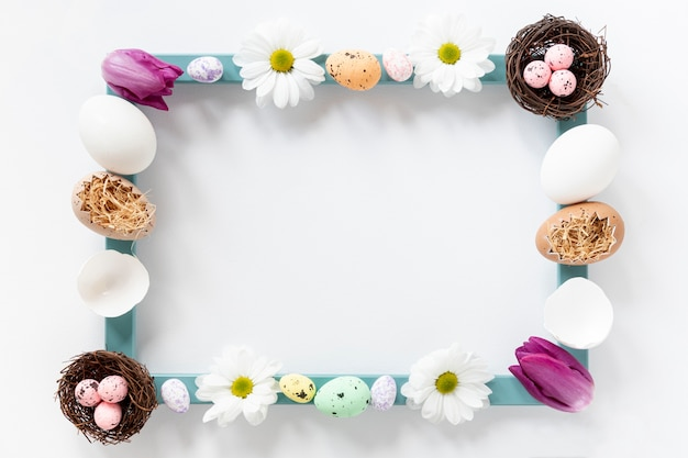 Flat lay frame made of flowers and eggs Free Photo