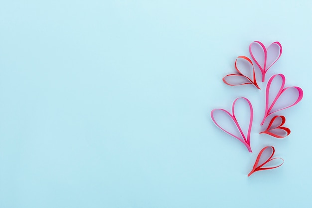 Flat lay frame with heart shapes and blue background Free Photo