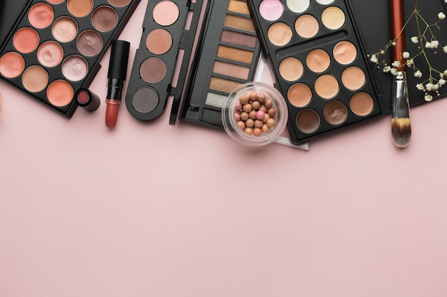 Flat lay frame with lipstick and make-up palettes Free Photo