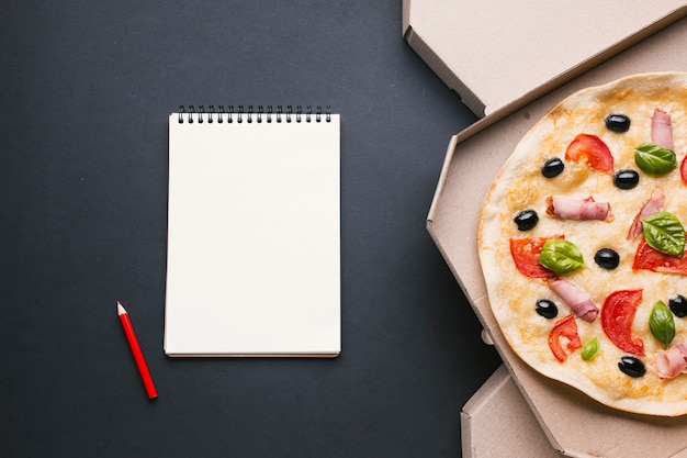 Flat lay frame with pizza and notebook Free Photo