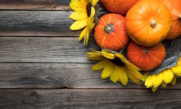 Flat lay frame with pumpkins on wooden background Free Photo