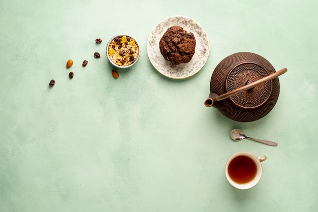 Flat lay frame with teapot and muffin Free Photo