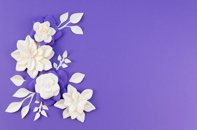 Flat lay frame with white flowers on purple background Free Photo