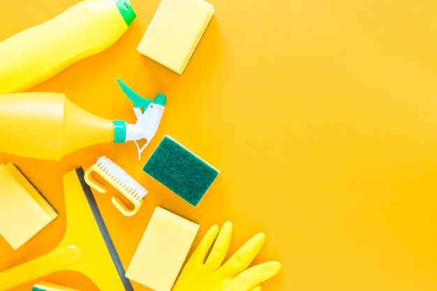 Flat lay frame with yellow cleaning products and background Free Photo