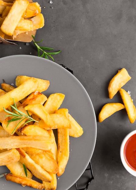 Lay piatto di patatine fritte sulla piastra con ketchup Foto Gratuite