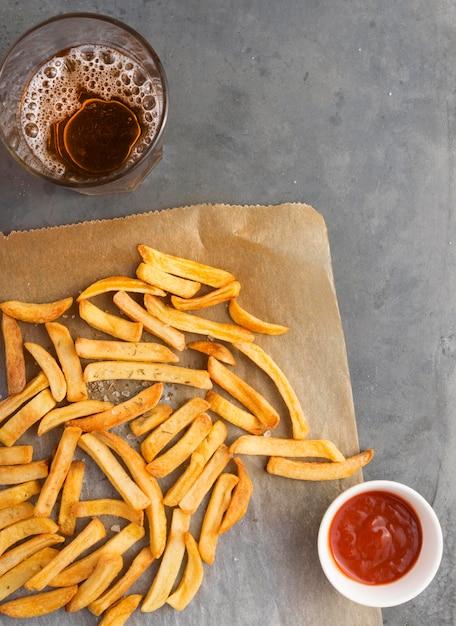Lay piatto di patatine fritte con ketchup e bibita gassata Foto Gratuite