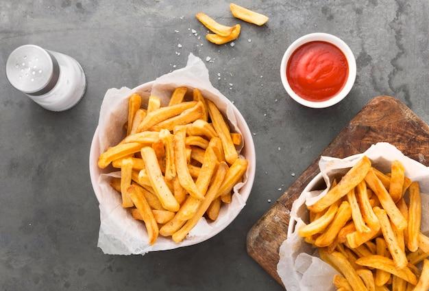 Lay piatto di patatine fritte con ketchup e saliera Foto Gratuite