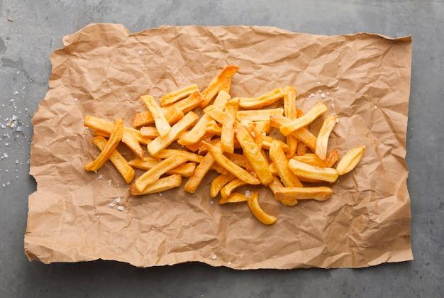 Lay piatto di patatine fritte con sale su carta Foto Gratuite