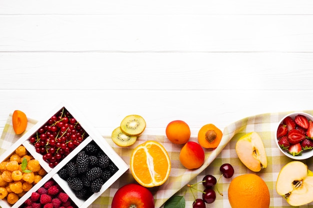 Flat-lay fresh berries and fruits with copy space Free Photo