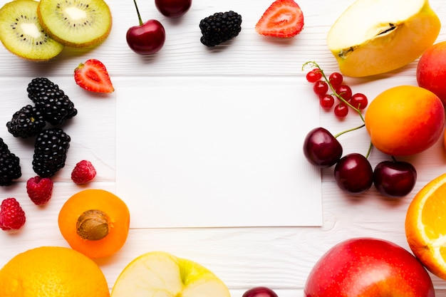 Flat-lay of fresh berries and fruits with paper Free Photo
