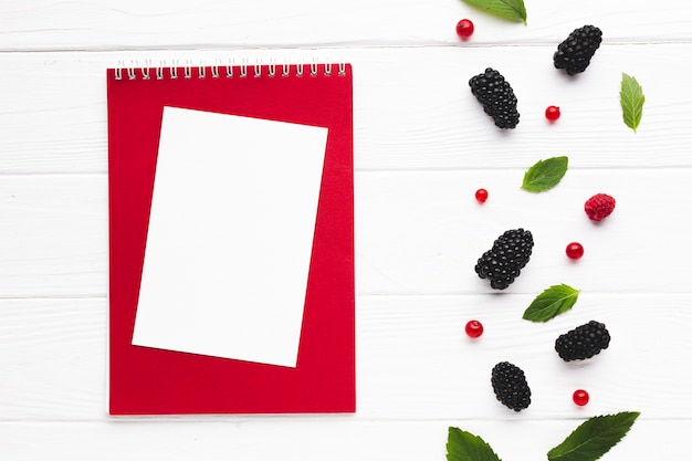 Flat-lay fresh berries with notepad Free Photo