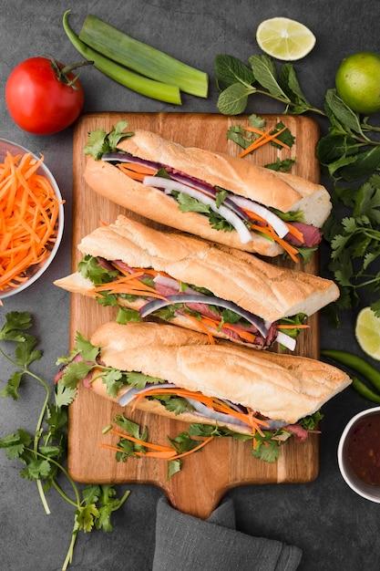 Flat lay of fresh sandwiches on chopping board Free Photo
