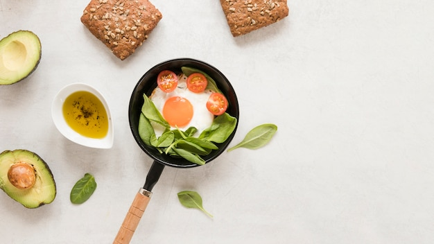 Flat lay fried egg in pan with tomatoes and avocado Free Photo