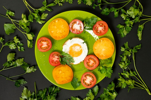 Flat lay fried egg with colorful tomatoes on plain background Free Photo