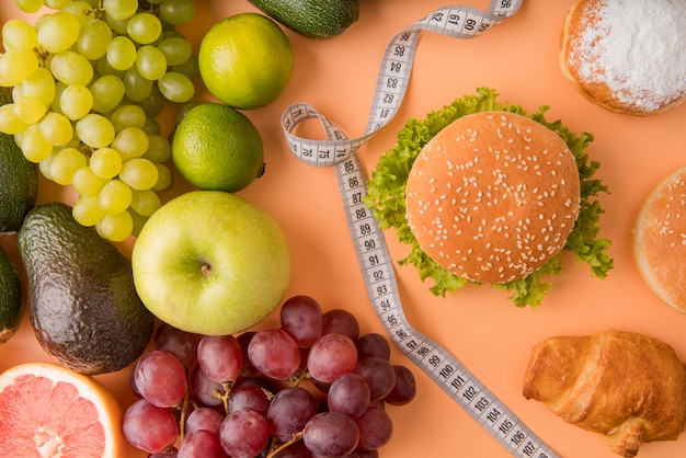 Flat lay fruits and unhealthy food with tape measure Free Photo