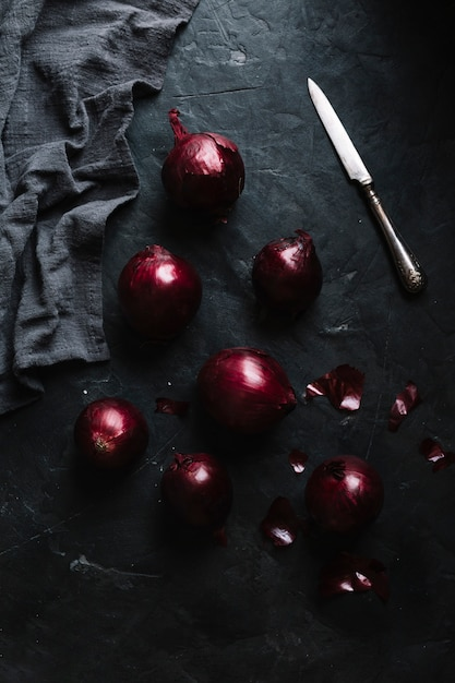 Flat lay full grown onions with black cloth Free Photo