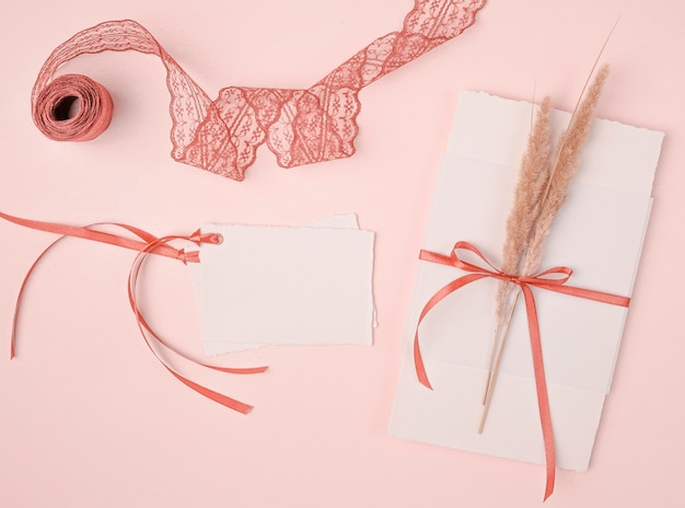 Flat lay girly arrangement for wedding invitations on pink background Free Photo