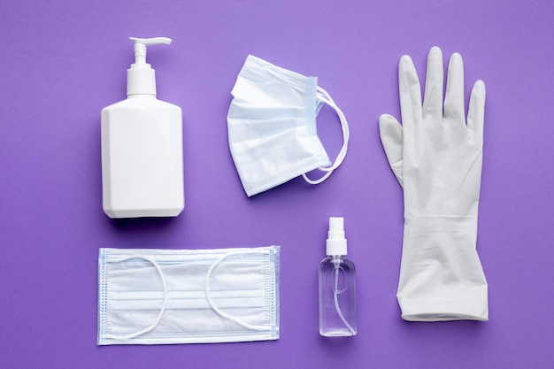 Flat lay of glove with medical masks and liquid soap bottle Free Photo