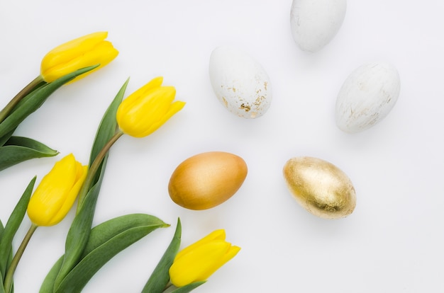 Flat lay of golden easter eggs with flowers Free Photo