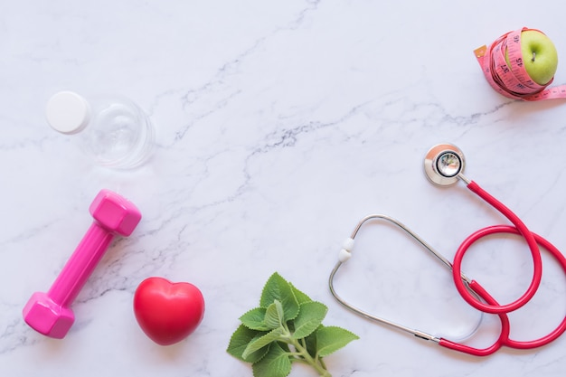 Flat lay of good healthy concept, pink dumbbell with red heart and stethoscope and green apple on white marble background Premium Photo
