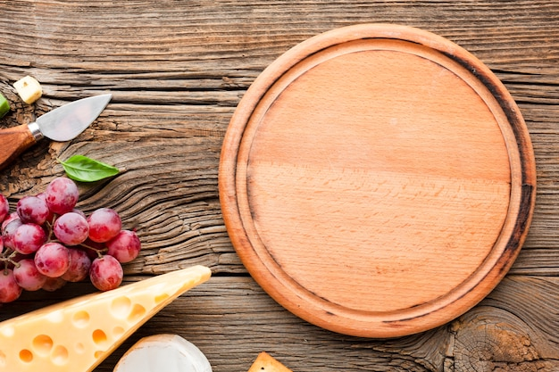 Flat lay grapes emmental and cheese knife with wooden cutting board Free Photo