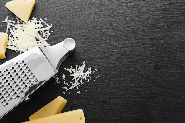Flat lay grated parmesan and grater with copy space Free Photo
