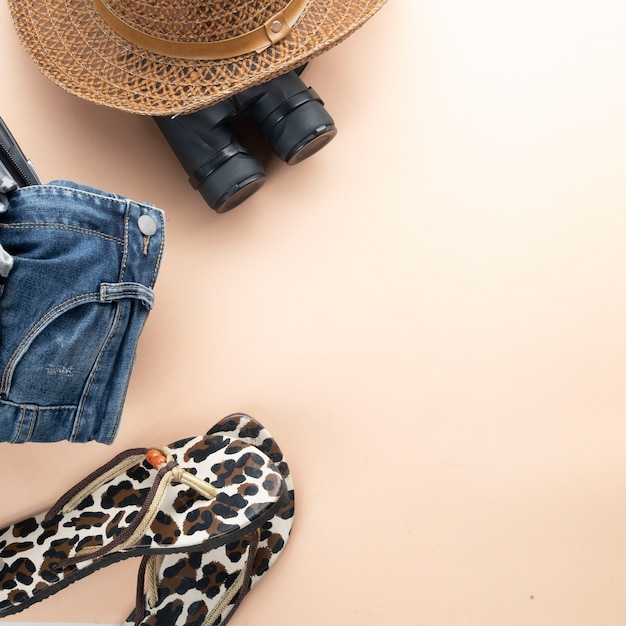 Flat lay grey suitcase with binoculars, hat, jeans and sandles. travel concept Premium Photo