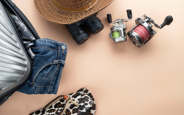 Flat lay grey suitcase with binoculars, hat, jeans, spinning for fishing and sandles. travel concept Premium Photo