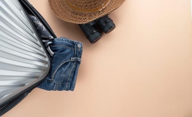Flat lay grey suitcase with binoculars, hat, jeans Premium Photo