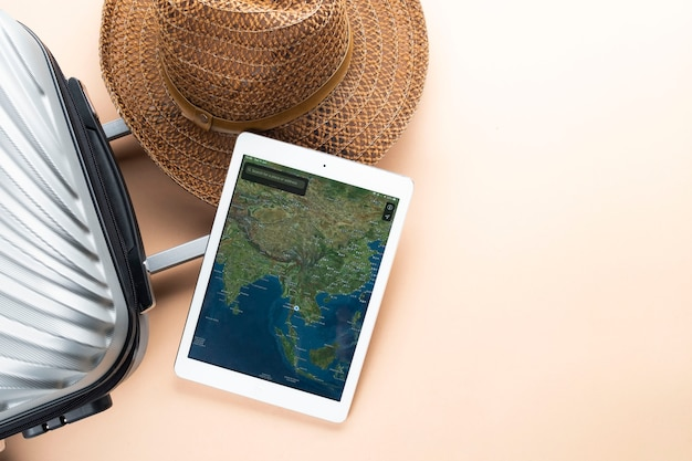 Flat lay grey suitcase with brown hat and map on gadget Premium Photo