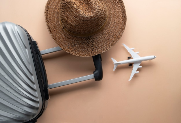 Flat lay grey suitcase with brown hat and mini airplane Premium Photo