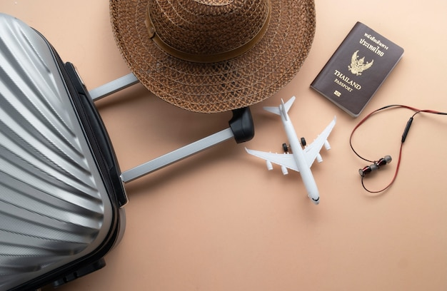 Flat lay grey suitcase with brown hat, mini airplane Premium Photo