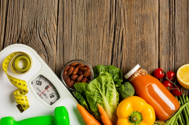 Flat lay of groceries and scale on wood table Free Photo