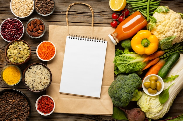 Flat lay of groceries with notebook mock-up Free Photo